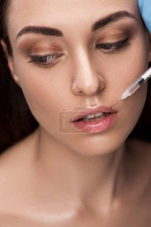 beautiful woman making beauty injection into lips