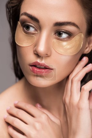 beautiful girl with golden collagen eye patches, isolated on grey