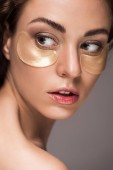 beautiful girl with golden eye patches, isolated on grey