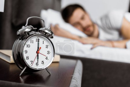 Photo pour Vue rapprochée du réveil et le jeune homme dort derrière - image libre de droit