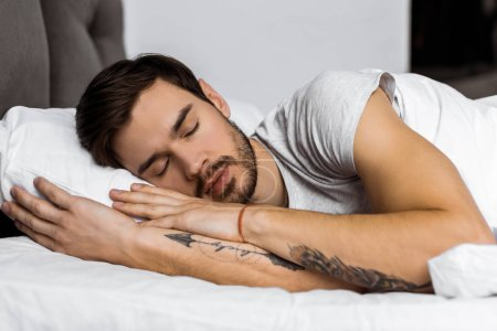handsome bearded tattooed young man sleeping in bed