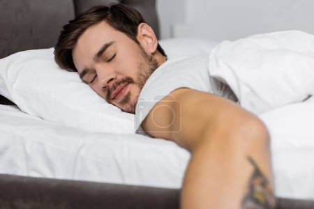 handsome bearded young man sleeping in bed