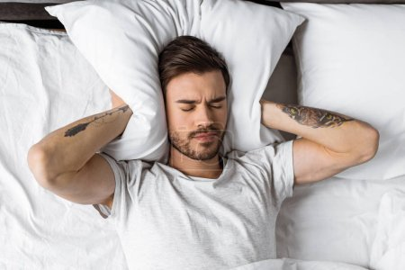 young man closing ears with pillow in bed in the morning