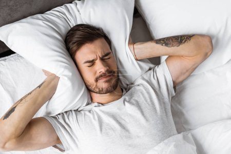 top view of young man closing ears with pillow in bed in the morning