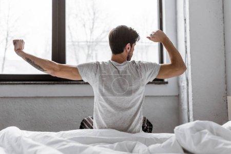 Photo pour Vue arrière du jeune homme en pyjama s'étirant assis au lit le matin - image libre de droit