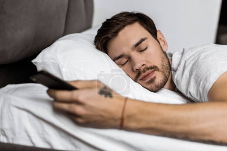 handsome bearded young man sleeping in bed with smartphone in hand