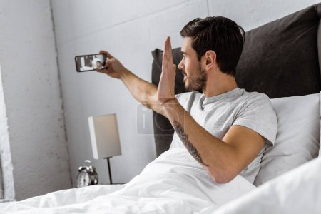 handsome young man chatting with smartphone and waving hand in bed