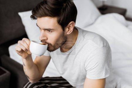 Foto de Vista de ángulo alto de joven sentado en la cama y tomar café en la mañana - Imagen libre de derechos