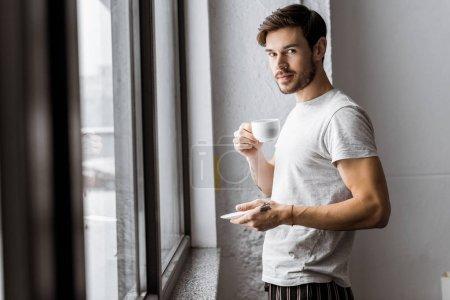 Photo pour Beau jeune homme tenant la tasse de café et de regarder la caméra en se tenant debout près de fenêtre le matin - image libre de droit