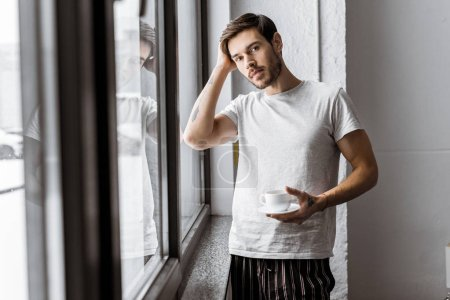 handsome young man holding cup of coffee and looking at camera in the morning