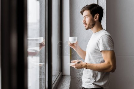 side view of young man holding cup of coffee and looking at window in the morning