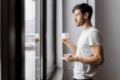 """Постер, картина, фотообои """"молодой человек, держа чашку кофе и глядя на окна по утрам, вид сбоку"""""""