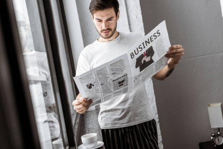 handsome young man reading business newspaper at home