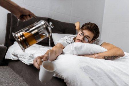 Photo pour Vue partielle d'une personne de verser le thé dans coupe homme endormi dans lunettes allongé sur le lit - image libre de droit