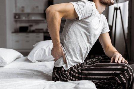 Foto de Recortado disparo de joven en pijama que sufre de dolor de espalda mientras está sentado en la cama por la mañana - Imagen libre de derechos