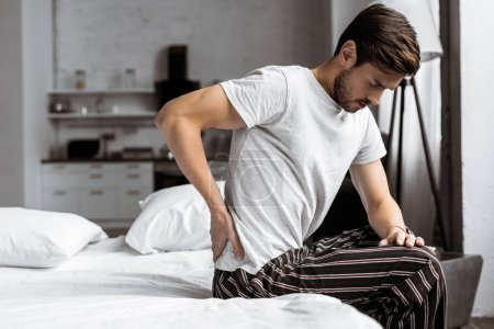 young man in pajamas suffering from backache while sitting on bed in the morning