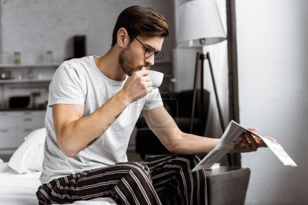 young man in pajamas and eyeglasses drinking coffee and reading newspaper in the morning