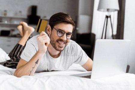 Foto de Atractivo joven sosteniendo la tarjeta de crédito y sonriendo a la cámara durante el uso de laptop en la cama - Imagen libre de derechos