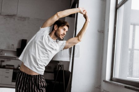 handsome young man in pajamas stretching and looking at window in the morning
