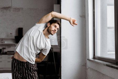Photo pour Beau jeune homme en pyjama faisant de l'exercice et regardant la fenêtre le matin - image libre de droit
