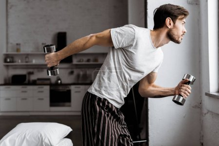 young man in pajamas holding dumbbells and looking at window at home