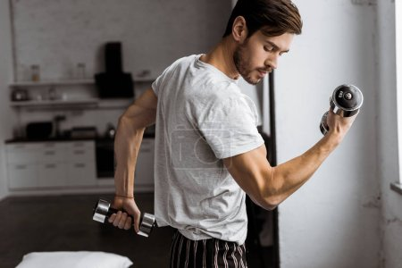 Photo for Handsome young man in pajamas exercising with dumbbells and looking at biceps at home - Royalty Free Image