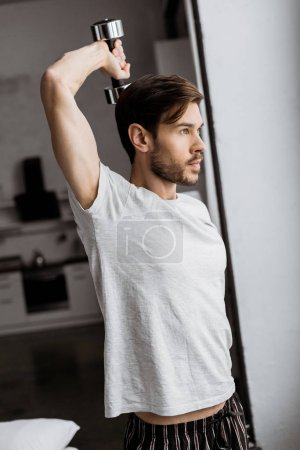 handsome young man in pajamas exercising with dumbbell and looking away in the morning