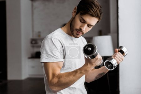 Photo for Handsome young man training with dumbbells and looking at biceps at home - Royalty Free Image
