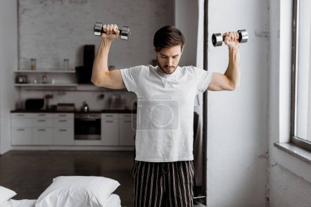handsome young man in pajamas exercising with dumbbells and looking down at home