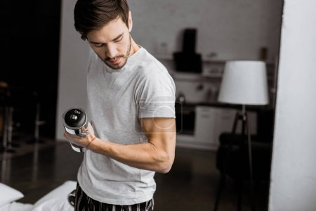 Photo for Handsome young man holding dumbbells and looking at biceps at home - Royalty Free Image