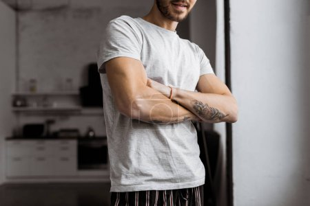 cropped shot of handsome young man with crossed arms in pajamas standing at home