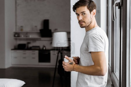 handsome young man with mug of coffee leaning back on window at home and looking at camera