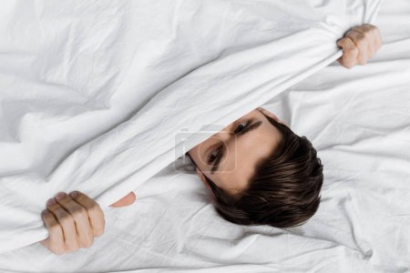 top view of handsome young man hiding under blanket in bed at home