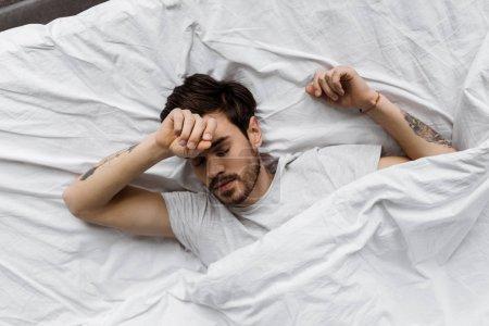Photo pour Vue de dessus du jeune homme endormi couché sous la couverture dans le lit à la maison - image libre de droit