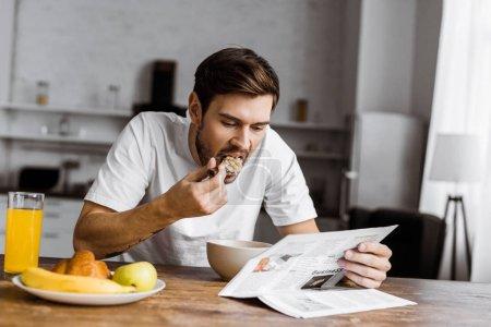 Foto de Hombre joven tener cereales para el desayuno y leyendo el periódico en casa - Imagen libre de derechos