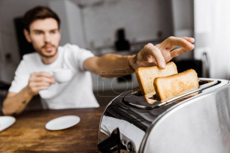 close-up shot of young man drinking coffee and taking toast from toaster