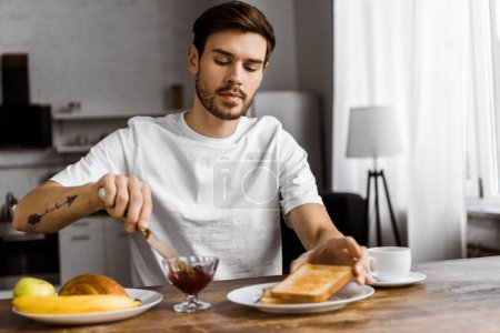 attractive young man applying jam onto toast on weekend morning at home