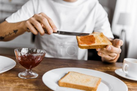 cropped shot of man applying jam onto toast at home