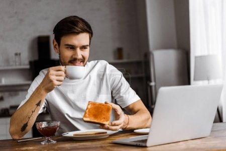 grimacing young freelancer eating toast with jam and looking at laptop screen at home