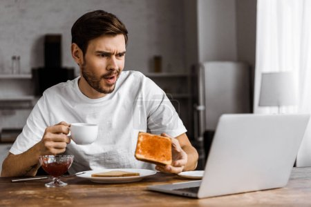 confused young freelancer eating toast with jam and looking at laptop screen at home