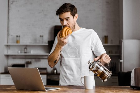 surprised young freelancer with cup of tea, croissant and laptop working on kitchen at home