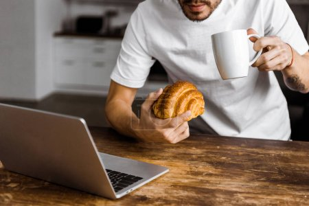 Photo for Cropped shot of attractive young freelancer with cup of tea, croissant and laptop working on kitchen at home - Royalty Free Image