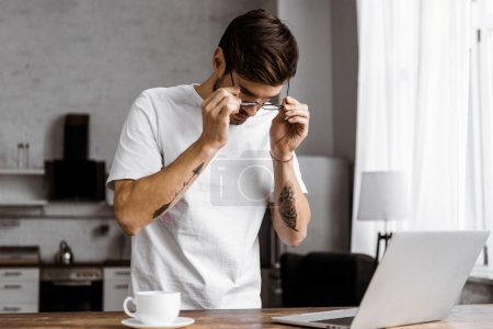 attractive young freelancer in eyeglasses with coffee and laptop on kitchen at home