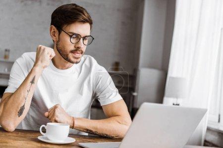 Photo pour Beau jeune freelance avec café de travail avec ordinateur portable à la maison - image libre de droit
