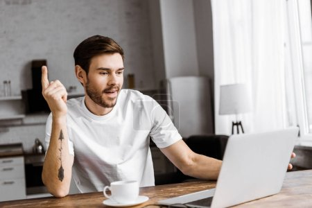 excited young man with coffee using laptop and looking up at home