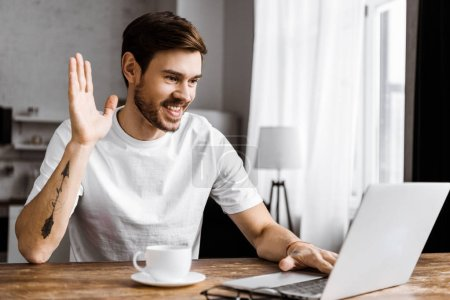 handsome young man with coffee making video call with laptop and waving at home