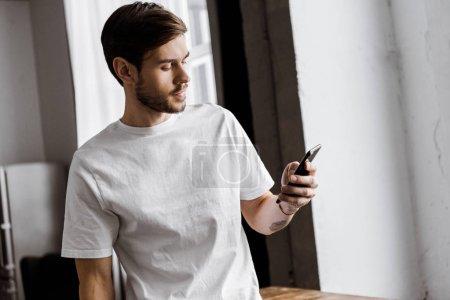 Photo pour Beau jeune homme utilisant un smartphone à la maison - image libre de droit