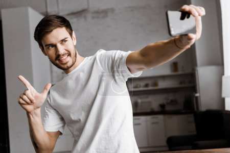 handsome young man taking selfie and making gun gesture at home