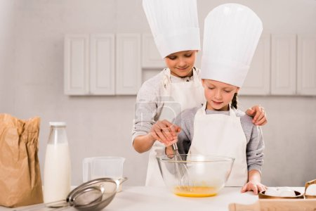 children in aprons and chef hats whisking eggs in bowl at table in kitchen