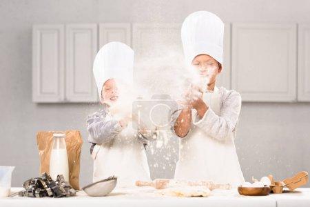 happy children in chef hats having fun with flour in kitchen
